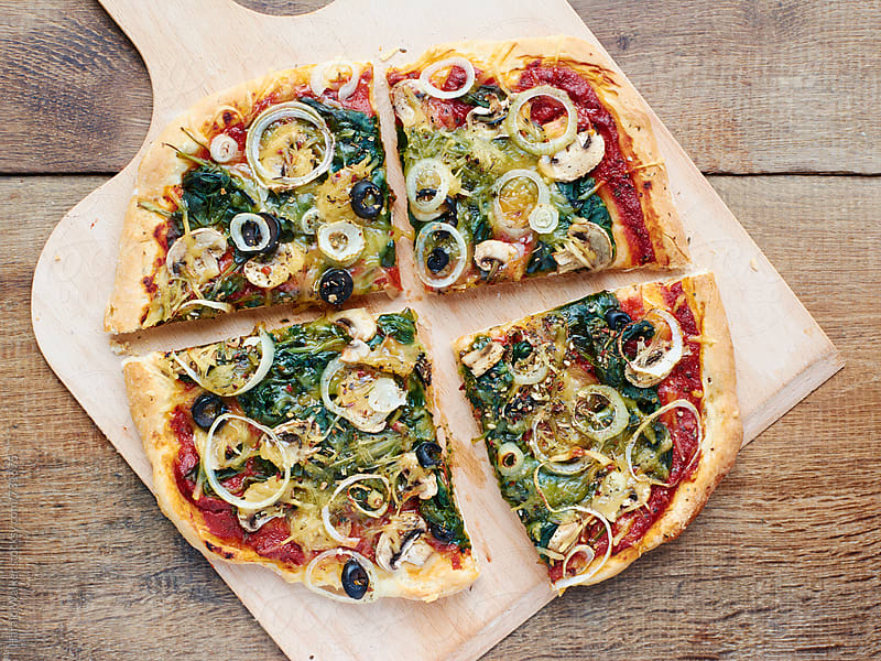 Spinach mushroom Pizza (vegan) by Harald Walker for Stocksy United