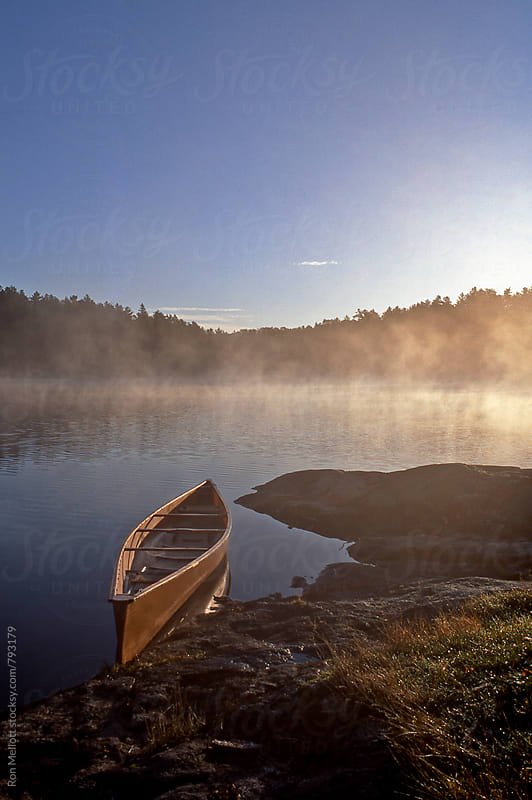 Canoe and calm lake at sunrise, Quetico Provincial Park, Ontario, Canada by Ron Mellott for Stocksy United