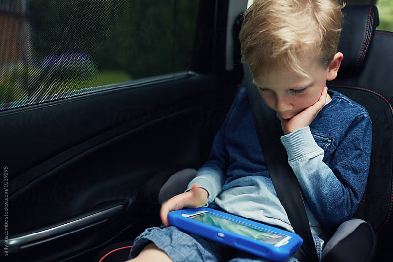 Child using an electronic tablet while in the car by sally anscombe for Stocksy United
