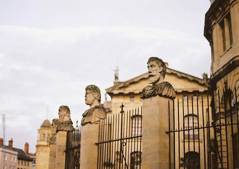 Stone heads outside the Sheldonian Theatre, Oxford.  by Kirstin Mckee for Stocksy United