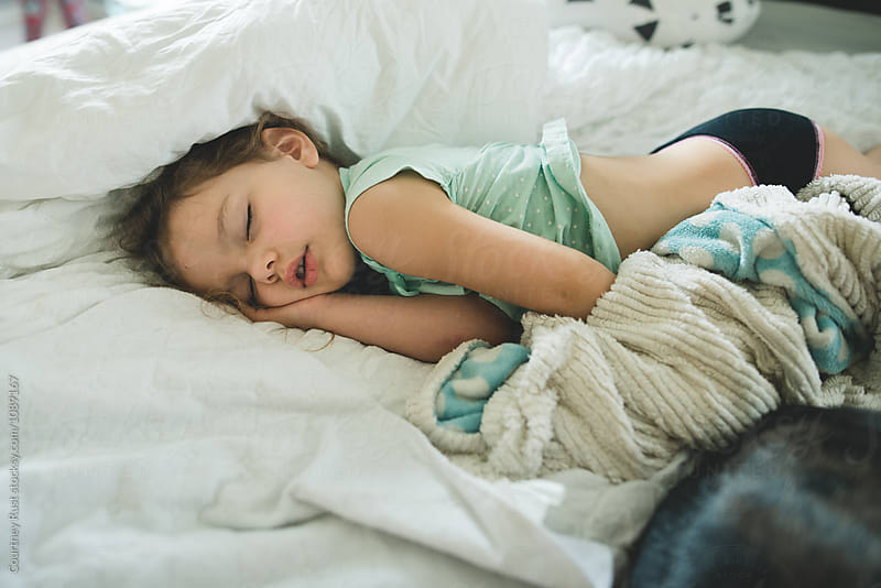 Toddler girl passed out in bed by Courtney Rust for Stocksy United