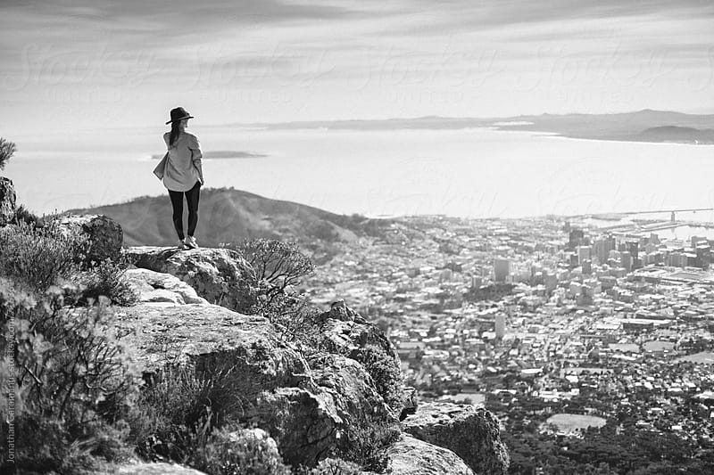 Young woman standing on edge of mountain cliff, overlooking city and ocean by Jonathan Caramanus for Stocksy United
