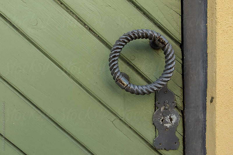 Oldfashioned door handle on a wooden door by Melanie Kintz for Stocksy United