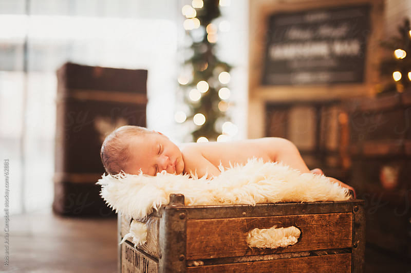 Newborn baby boy sleeping on old box by Rob and Julia Campbell for Stocksy United