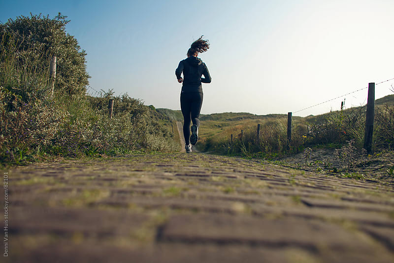 Young woman running over a path through the dunes during her workout by Denni Van Huis for Stocksy United