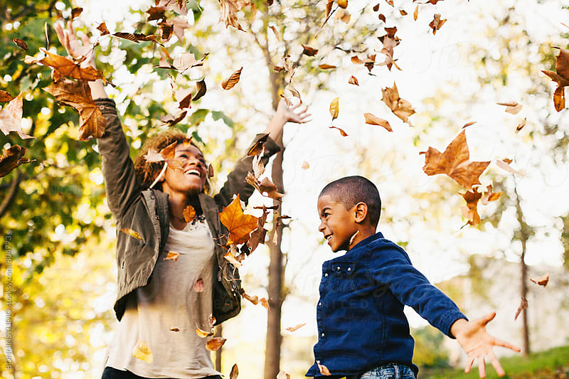 Mother and her son playing with autumn leaves in the park. by BONNINSTUDIO for Stocksy United