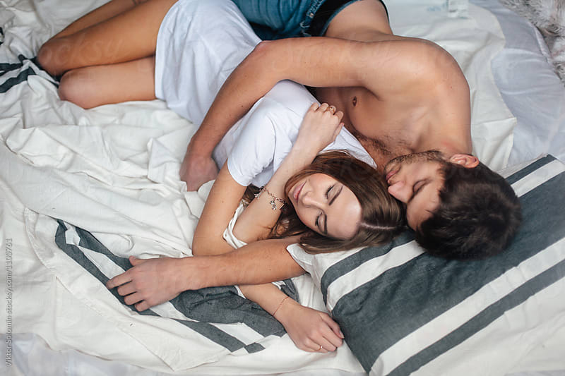Young couple lying in bed by Viktor Solomin for Stocksy United
