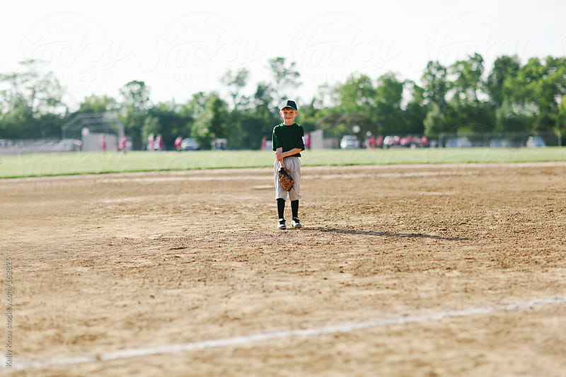 baseball player standing in the field by Kelly Knox for Stocksy United