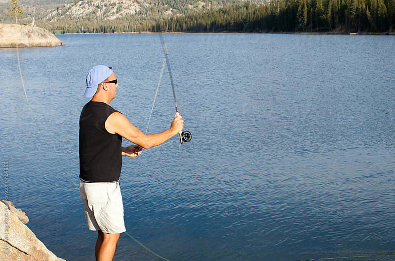Man fly fishing in a lake during summer by Carolyn Lagattuta for Stocksy United