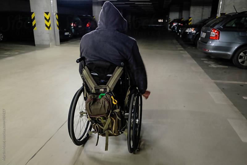 Man on wheelchair going through garage by Martin Matej for Stocksy United