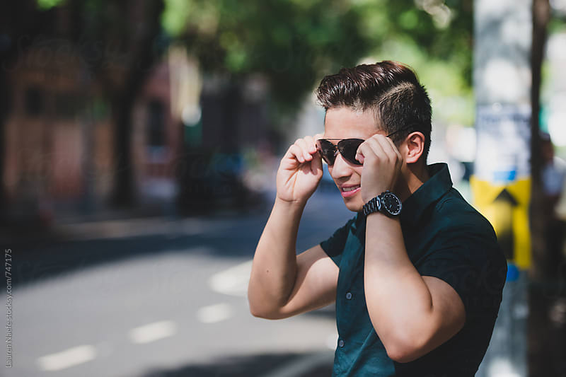 Young man putting on sunglasses by Lauren Naefe for Stocksy United