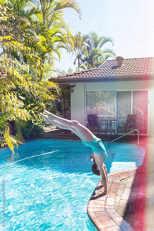 girl doing a handstand into the pool by Gillian Vann for Stocksy United