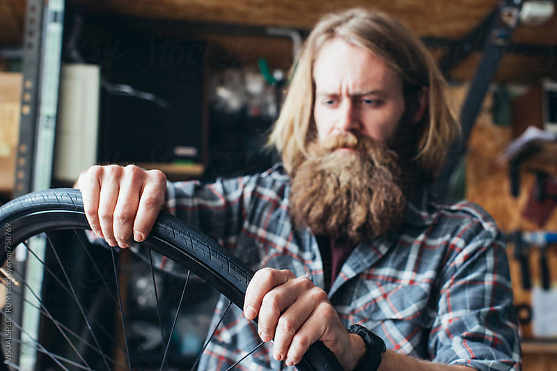 Young Bearded Hipster Mechanic Assembling Tube and Tire on Bicycle Wheel by Julien L. Balmer for Stocksy United