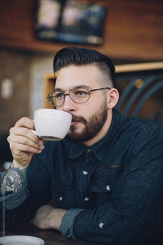 Stylish young man drinking coffee by Ania Boniecka for Stocksy United