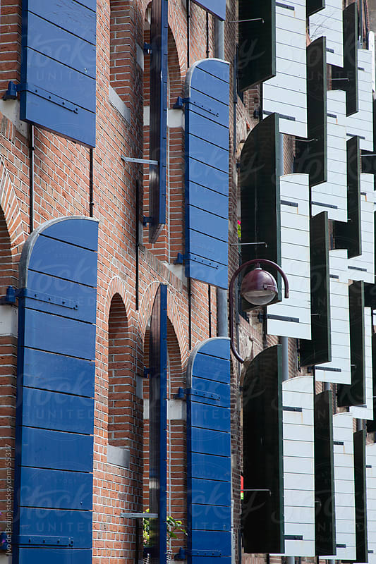 The facades of two brick mansions with white and  blue shutters in Amsterdam by Ivo de Bruijn for Stocksy United