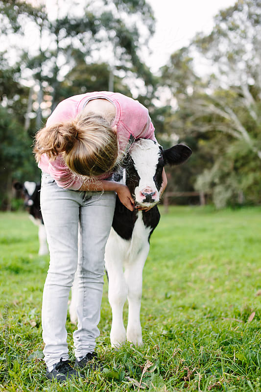 Teen girl hugs a calf by Jacqui Miller for Stocksy United