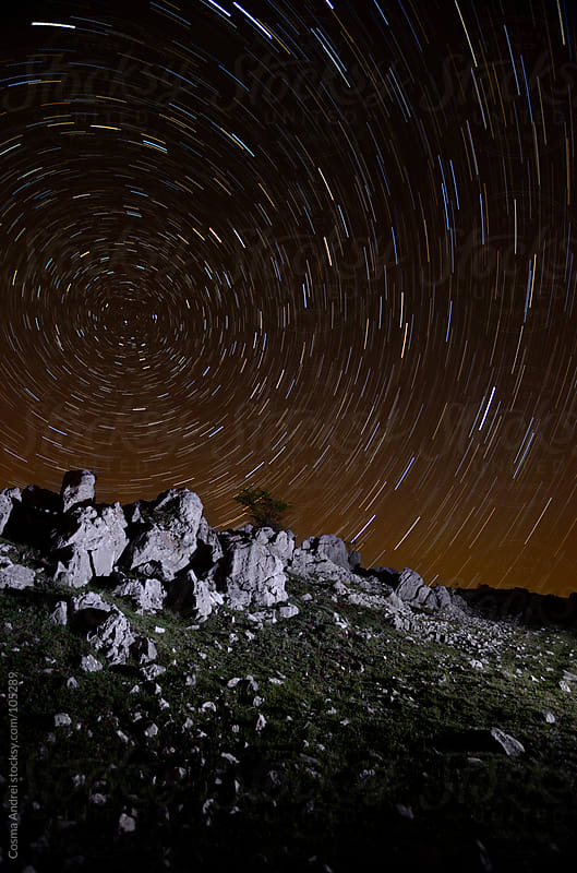 Night photo with star trails over mountain cliffs by Cosma Andrei for Stocksy United