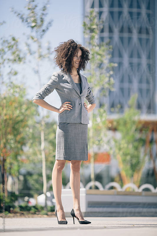 A confident businesswoman with hands on hips by Ania Boniecka for Stocksy United