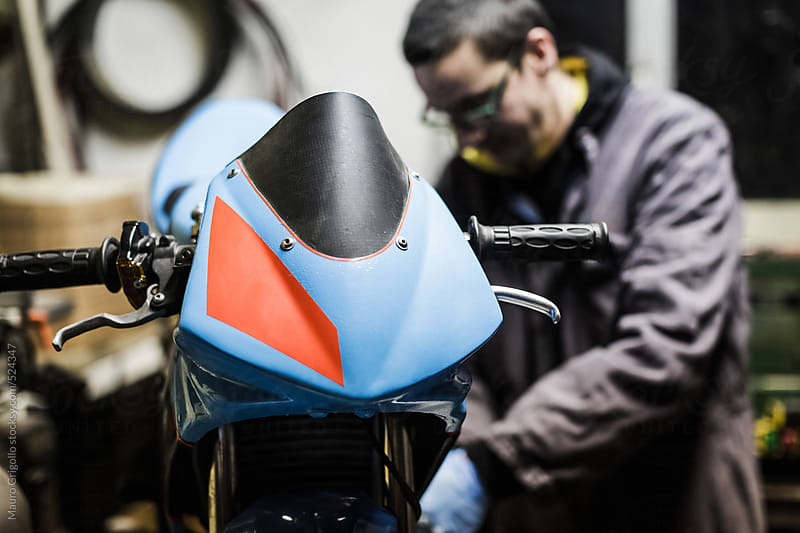 Mechanical operator works on mini motorbike by Mauro Grigollo for Stocksy United