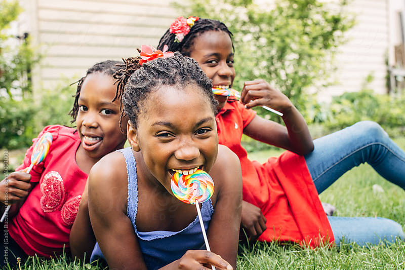 Three black girls with lollipops laughing by Gabriel (Gabi) Bucataru for Stocksy United