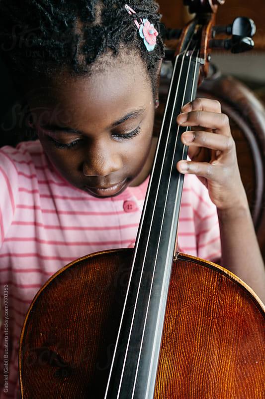 Black girl practicing cello at home by Gabriel (Gabi) Bucataru for Stocksy United