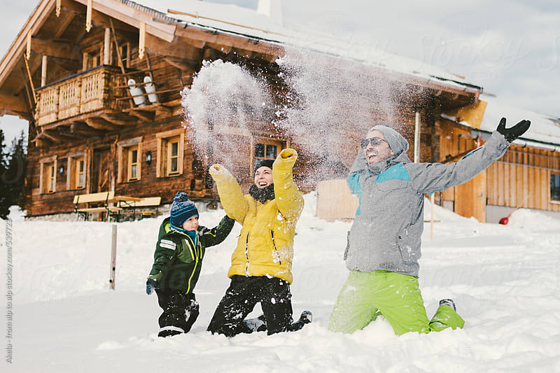 happy family throwing snow with alpine cabin in the back by Leander Nardin for Stocksy United