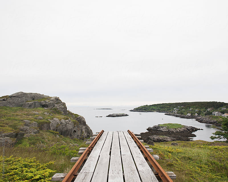 A wooden path descends to a rugged coastline by TJ Macke for Stocksy United