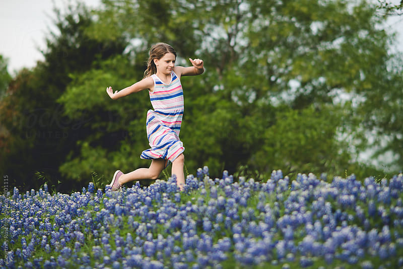 girl running through the bluebonnets by Courtney Rust for Stocksy United