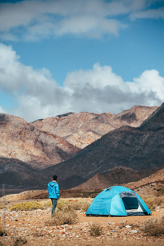Hiker outside his tent in a rugged mountain landscape by Micky Wiswedel for Stocksy United