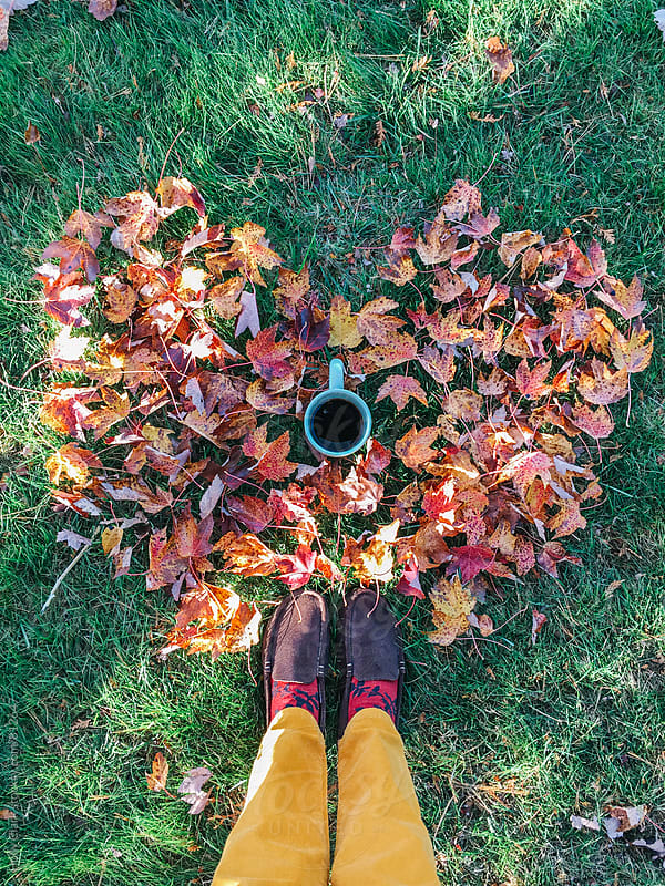 Cup of coffee sitting on grass inside a heart made of fall leaves by Holly Clark for Stocksy United