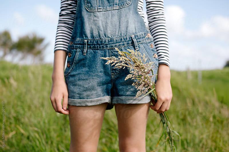Girl holding long flowering grass in her hand by Jacqui Miller for Stocksy United
