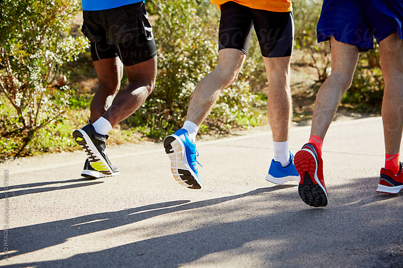 Low Section Of Male Athletes Running On Street by ALTO IMAGES for Stocksy United