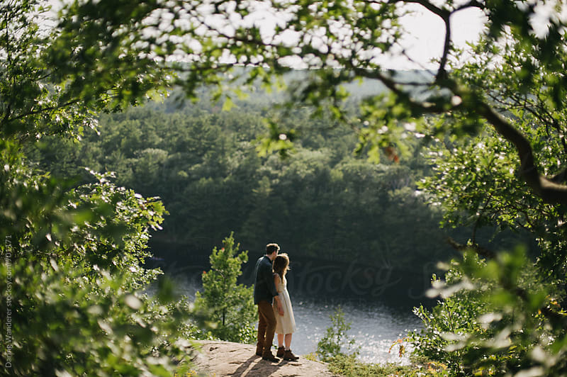 Fun adventurous intimate engaged couple on lookout over forest landscape by Daring Wanderer for Stocksy United