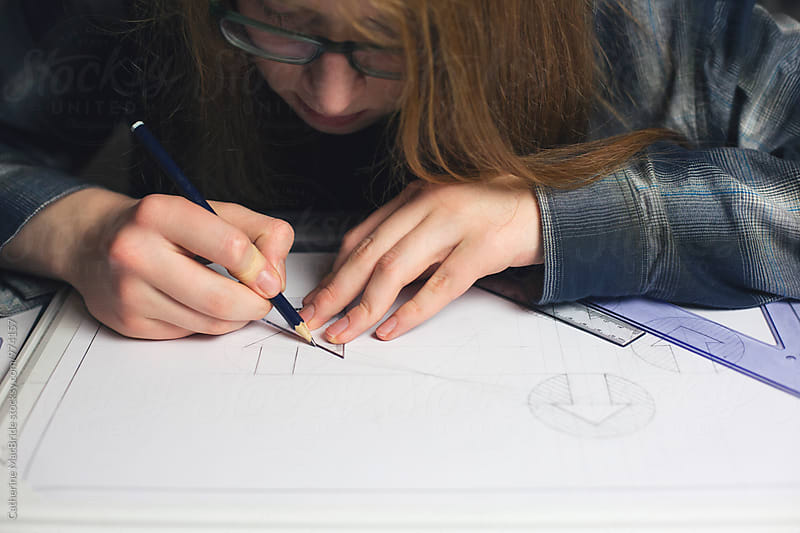 Long haired teenage boy drawing technical graphics... by Catherine MacBride for Stocksy United
