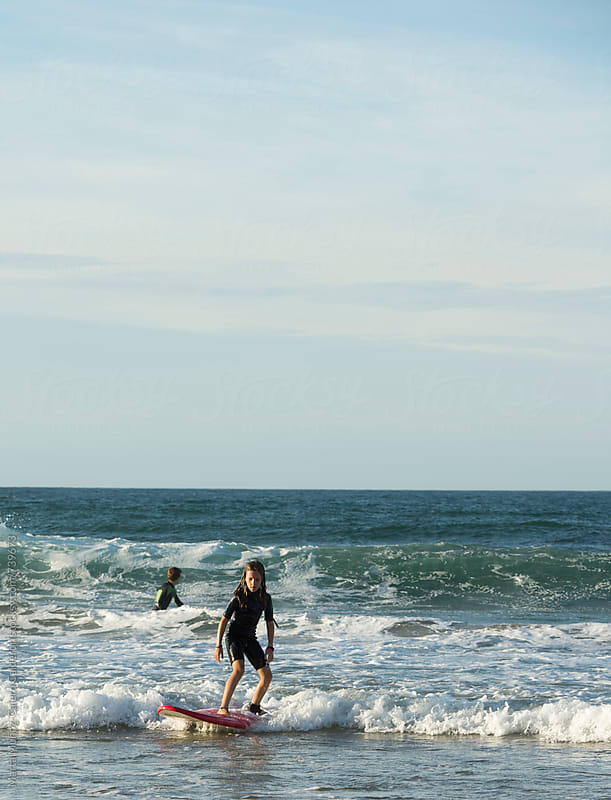Girl learning how to surf by Marta Muñoz-Calero Calderon for Stocksy United