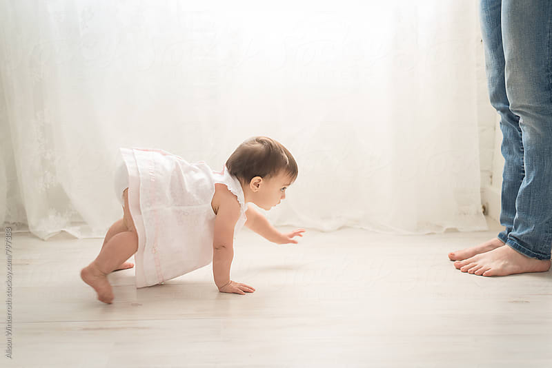A Little Girl Crawling To Her Mother's Legs by Alison Winterroth for Stocksy United