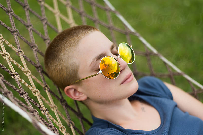 Portrait of woman with retro sunglasses lay on sunbed by Katarina Simovic for Stocksy United