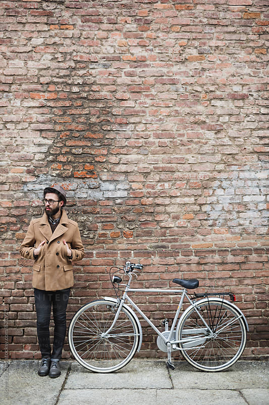 Man standing beside his bicycle in front of a brick wall by michela ravasio for Stocksy United
