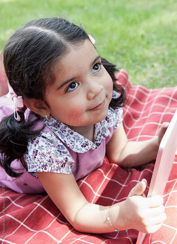 Cute young girl playing with computer tablet in a park by W2 Photography for Stocksy United