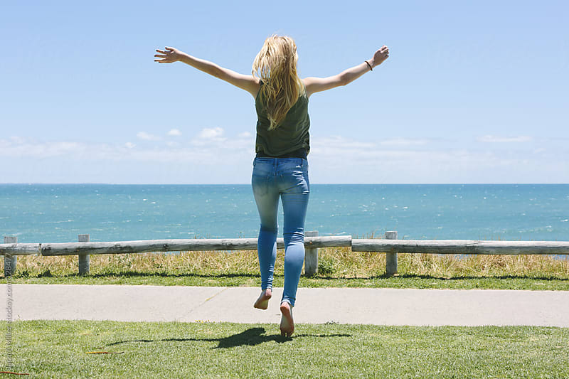 Teenage girl jumping for joy as she runs toward a view of the ocean.  by Jacqui Miller for Stocksy United