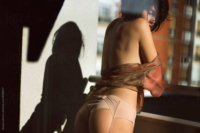 sensual woman from the back on the balcony by Sonja Lekovic for Stocksy United
