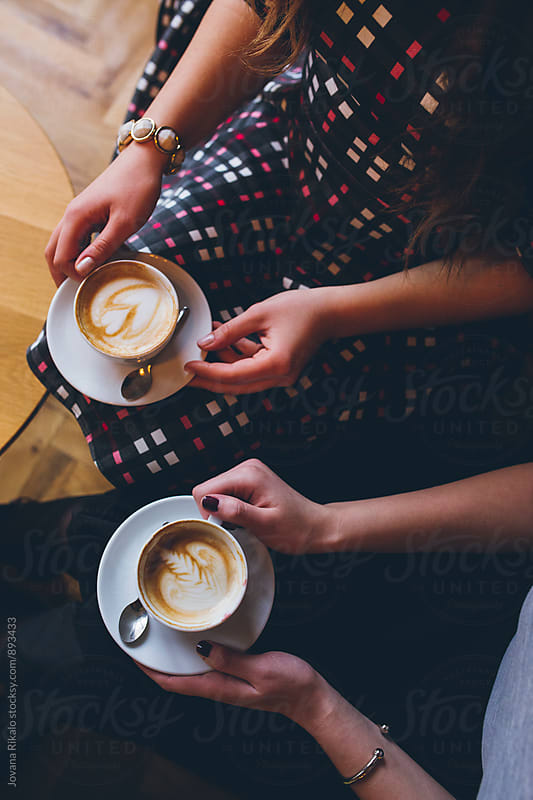 Two female friends drinking coffee by Jovana Rikalo for Stocksy United