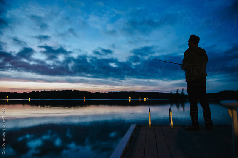 Man fishing on a lake at sunset by Cara Dolan for Stocksy United