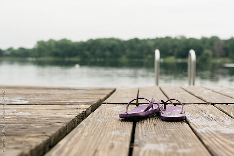 Pair of purple flip flops on a deck by a lake by Gabriel (Gabi) Bucataru for Stocksy United