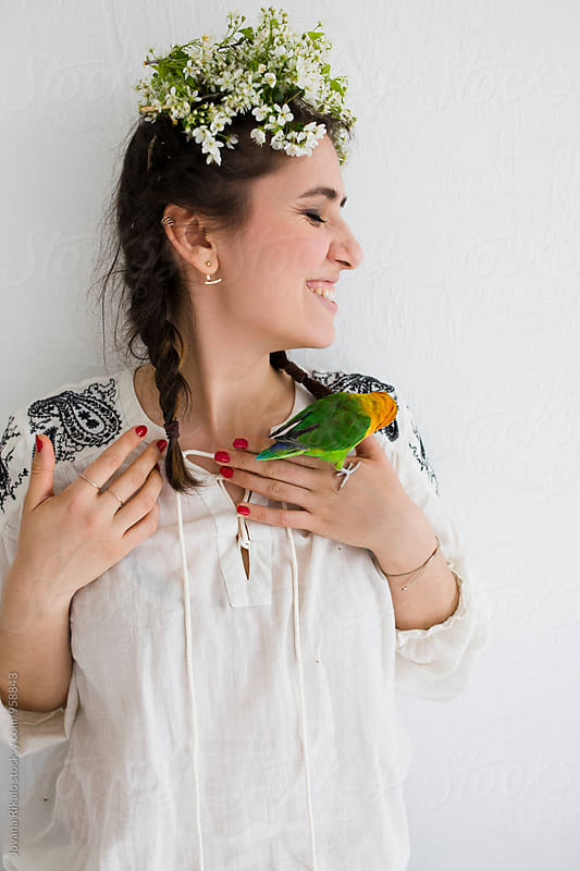 Portrait of a young woman and a parrot by Jovana Rikalo for Stocksy United
