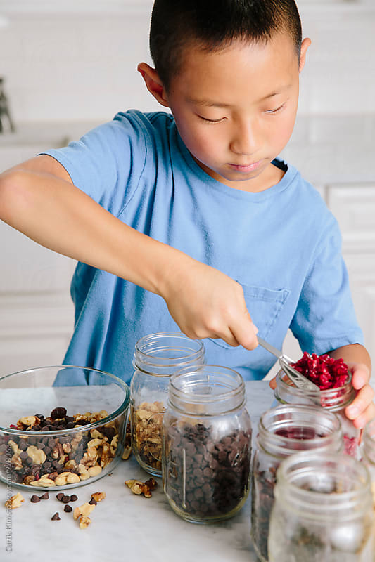 Boy mixing nuts and dried fruits by Curtis Kim for Stocksy United