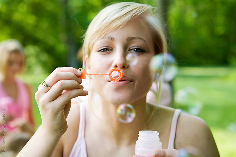 Charity Walk: Blowing Bubbles at Camera by Sean Locke for Stocksy United