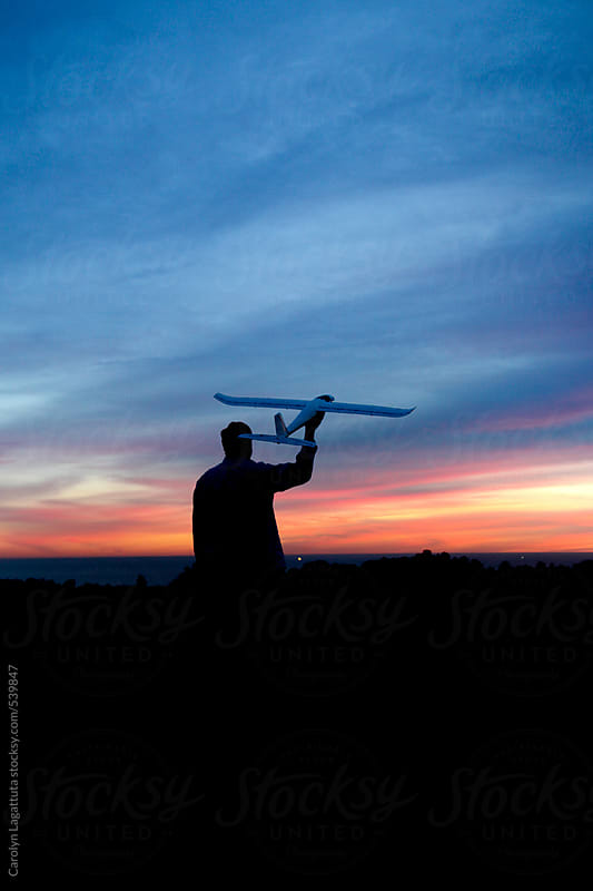 Silhouette of a man holding a large remote control plane at sunset by Carolyn Lagattuta for Stocksy United