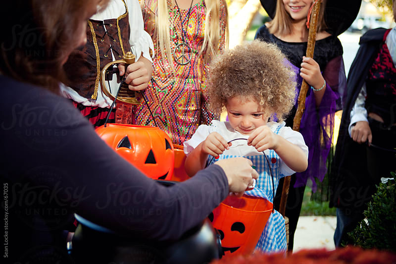 Halloween: Little Girl Excited to Get Candy by Sean Locke for Stocksy United