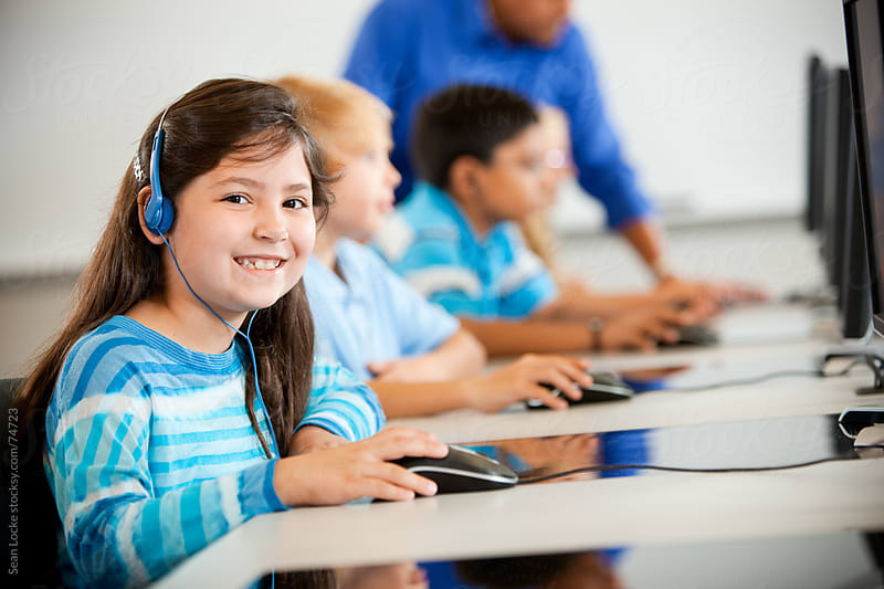 Computer Class: Young Girl Wears Headphones in Class by Sean Locke for Stocksy United